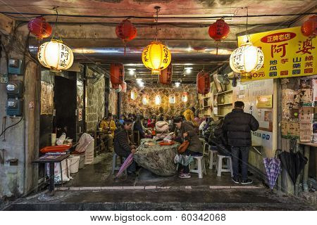 JIUFEN, TAIWAN - JANUARY 17, 2013: Tourists enjoy local cousine in Jiufen. The town is a tourist attraction reknown for a its unique atmosphere.