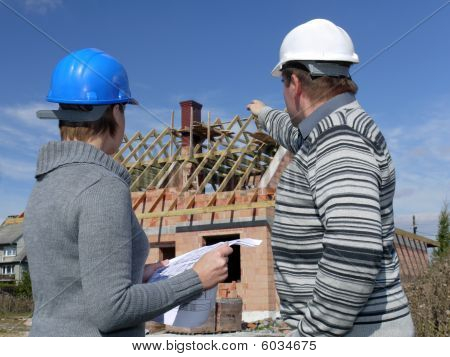 Female and male building engineers wearing helmets discussing building plans over unfinished brick house man pointing at the building poster