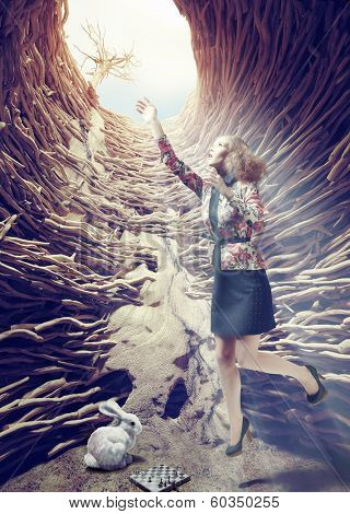 Girl flies out of a deep hole toward the sunlight. Creative concept