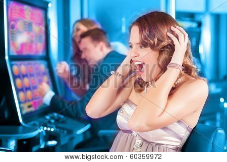 Friends gambling in Casino on slot machine, a woman is winning