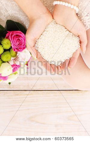 A picture of white rice in hands of a bride over wooden floor