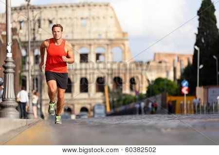 Running runner man by Colosseum, Rome, Italy. Male athlete training for marathon jogging in city of Rome in front of Coliseum in full body length. Fit male sport fitness model jogger in run outside.