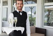 Handsome smiling waiter holding tray of champagne in the patio of restaurant poster
