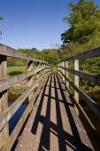 Small wooden bridge accross the river North Tyne in Northumberland near featherstone Castle. poster