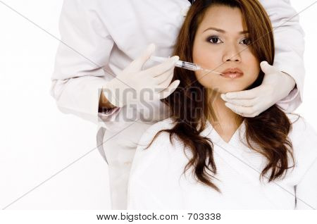 A young woman about to have an injection in her lips poster