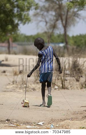 BOR, SOUTH SUDAN-FEBRUARY 25 2013: Unidentified boy plays with home made toy in the village of Bor, South Sudan