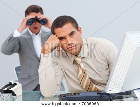 Handsome businessman getting bored and his manager looking through binoculars in a office poster