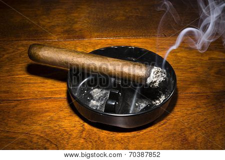 A burning cigar in a classic black ashtray streaming smoking in a dark, moody setting. The smoke is real, straight from the cigar and not put in later during post processing. poster