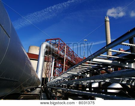 Industrial Zone, Steel Pipelines And Smokestack On Blue Sky