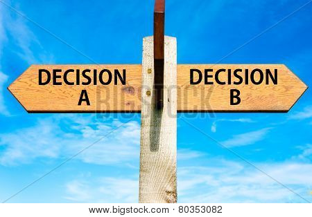Wooden signpost with two opposite arrows over clear blue sky Decision A and Decision B messages Right choice conceptual image poster