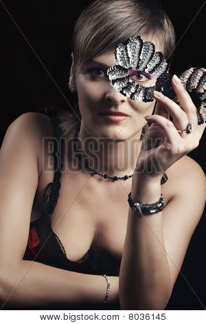 Stylish young woman holding glitter mask against dark background with selective focus poster