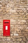 traditional old English red postbox mounted in a cotswold stone wall poster