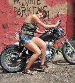 Biker gal posing on her motorcycle outdoors. poster