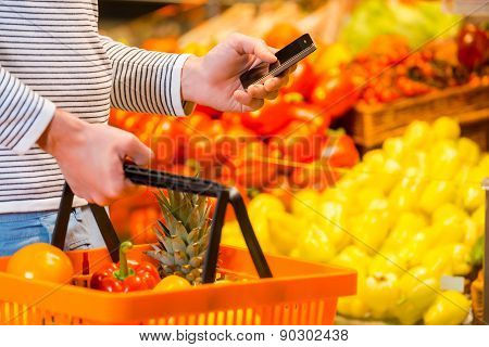Closeup of young man holding shopping basket and mobile phone