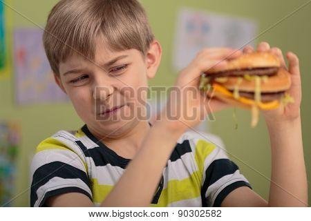 Unhealthy lunch - boy won't eat hamburger at school poster