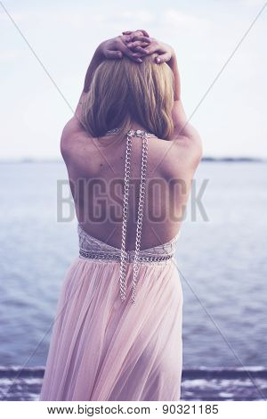 Back potrait of beautiful blond curly woman wearing evening peach color gown at lake.Fashionable and glamorous dress with chains. poster