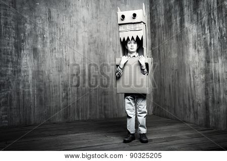 Black-and-white portrate of a dreamer boy playing with a cardboard dragon, dinosaur. Childhood. Fantasy, imagination. Retro style.
