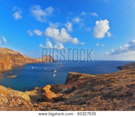 Quiet ocean cove on the island of Madeira. White yachts lit sunset. Calm on the Atlantic Ocean poster