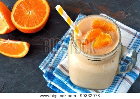 Orange fruit smoothie in a mason jar over slate background
