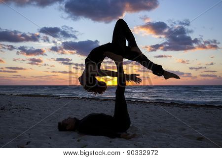 Couple practicing acroyoga at sunrise