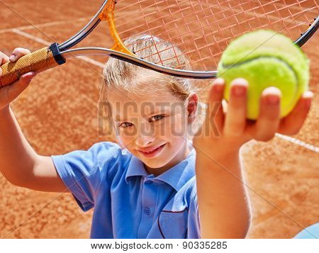 Child girl with racket and ball on  tennis court.