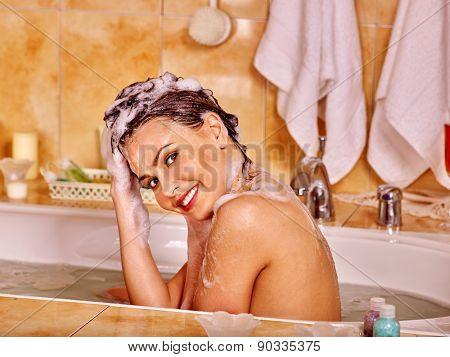 Happy woman washing hair in bubble bath. A  lot of water.