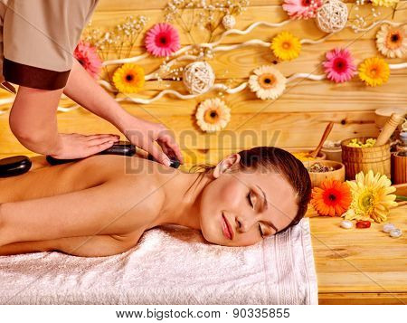 Happy woman getting stone therapy massage in spa. Herbera flower on wooden wall.