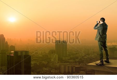Business Man And Binocular Spying Acting Standing On Top Of Office Building And Watching Lens To Ano