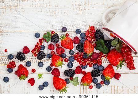 Fresh summer berries in vintage mug over wooden background,top view