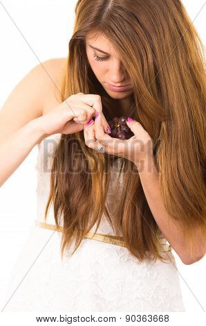 Beautiful young supersticious woman eating grapes