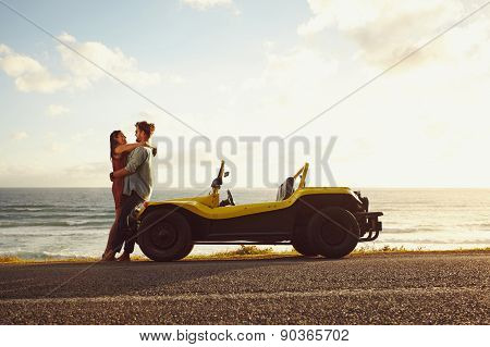 Young couple in love embracing each other on road trip in nature. Beautiful view of romantic young couple alongside their beach buggy and sea in background on a bright summer day. poster