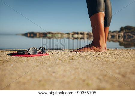 Swim Goggles On The Sand With A Woman Standing By