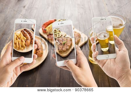 Friends Using Smartphones To Take Photos Of Sausage And Pork Chop And Beer
