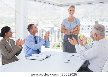 Business team applauding their colleague in the office