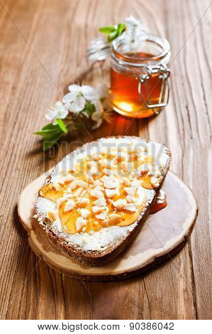 Bread with butter and honey on wooden background