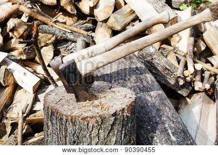 stack of wood deck for chopping firewood ax and cleaver on rustic courtyard poster
