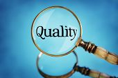 Magnifying glass focus on word quality concept for quality control, customer satisfaction and excellence poster