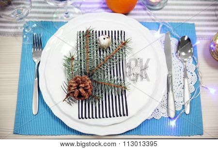 White plates with flatware on a Christmas table, close up
