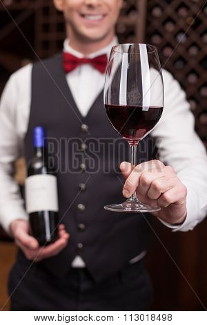 Cheerful young sommelier is serving a customer