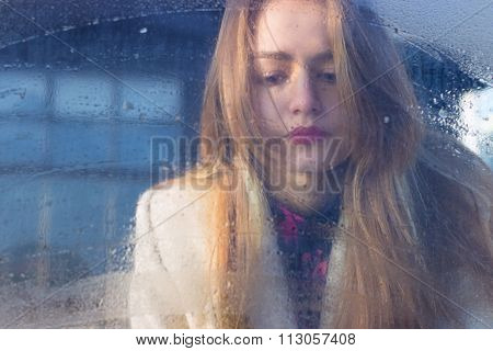 sad beautiful seksalnaya Pretty sad lonely girl behind wet glass with big sad eyes in a coat