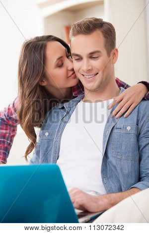 Attractive married couple is entertaining with a notebook