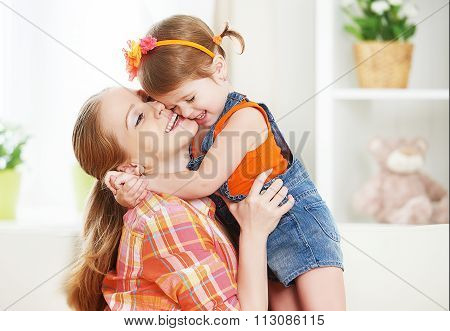Happy Family Mother And Child Girl Daughter Playing  Laughing And Hugging