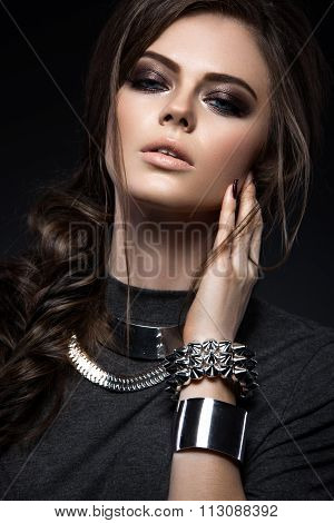 Beautiful girl with bright smokey make-up, perfect skin, black clothes, metal accessories and hairst