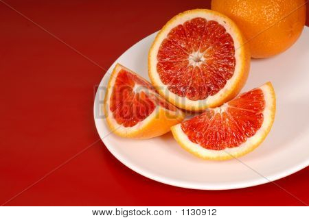 Whole And Cut Up Blood Oranges On White Plate