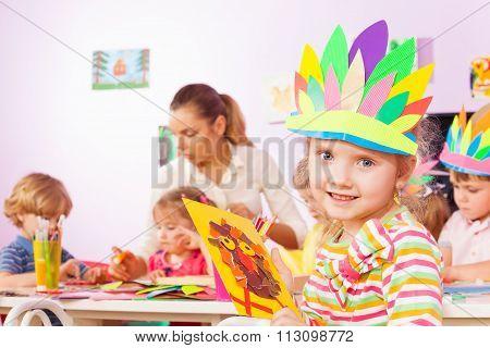 Little girl with her craft in kindergarten class