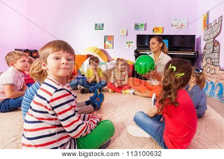 Kids and teacher sit in circle