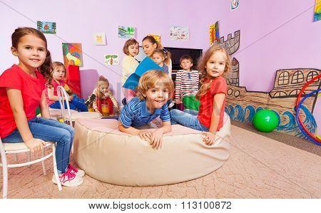 Group of kids listen to the teacher reading a book
