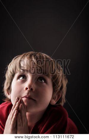 Young boy praying, low key lighting.