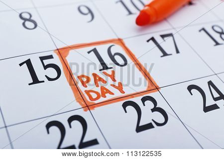 Payday concept. Calendar with orange felt pen background. Date in frame, close up