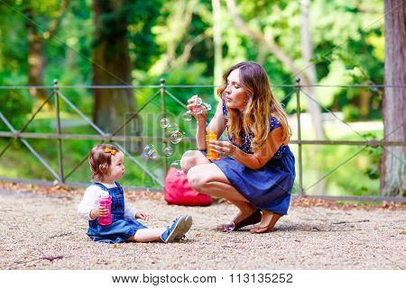 mother and little girl blowing soap bubbles in park